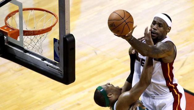 Le Bon James, a la izquierda, lanza sobre el jugador de los Celtics, Paul Pierce, en el tercer cuarto del juego