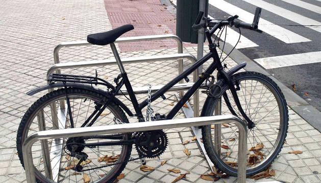 Una bicicleta, en un aparcamiento para bicicletas