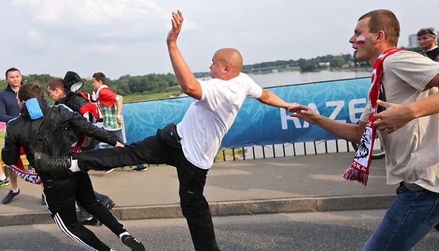 Un aficionado polaco lanza una patada a uno ruso durante los disturbios que tuvieron lugar sobre el puente del Vístula antes del encuentro de la Eurocopa 2012 entre Polonia y Rusia