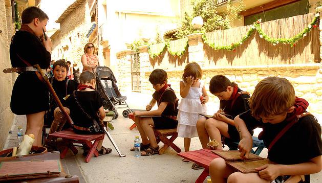 Niños usando tablas de cera en la escuela romana