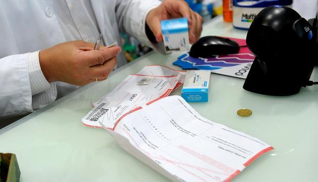 Un farmacéutico, dispensando medicamentos a un pensionista, este domingo