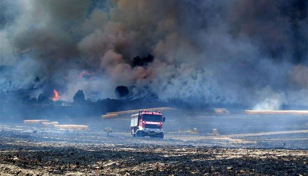 Un camión de bomberos recorre parte de la superficie quemada