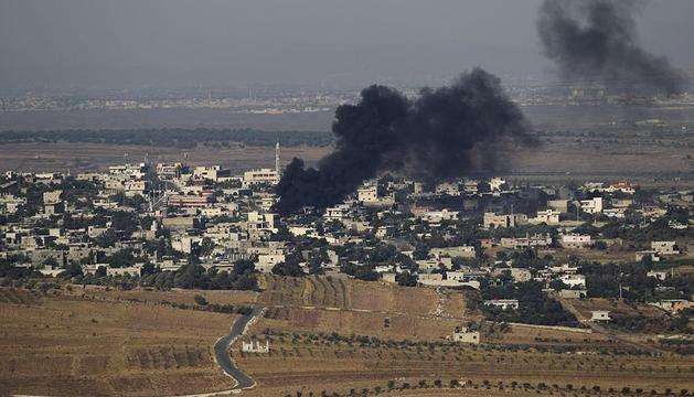 Vista general de una columna de humo tras un ataque este jueves al pueblo sirio de Jbatha Al-khashab