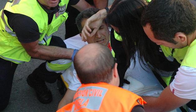 Juan Carlos Martínez Villafranca, con gesto de dolor, es atendido sobre la camilla por varios sanitarios.