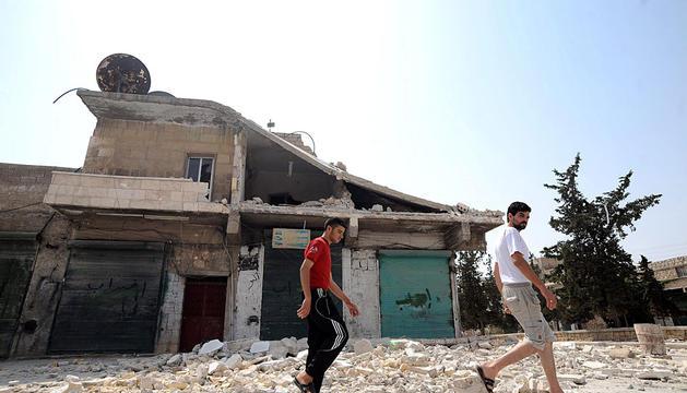 Dos hombres caminan frente a un edificio destruido en una calle de Aleppo.