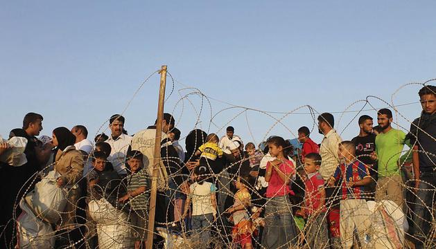Refugiados sirios, que huyeron de la violencia en su país, haciendo cola en la frontera siria con Turquía, en Hatay