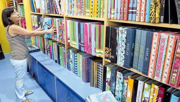 Juana Chacón Marín, propietaria de la librería-pepalería Tucán en la calle Tafalla, ordenando  unas carpetas clasificadoras.