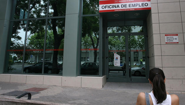 Una joven espera a las puertas de una oficina de empleo.