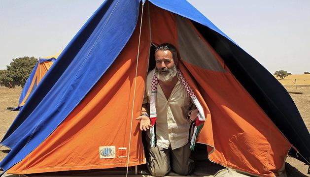 El diputado Juan Manuel Sánchez Gordillo asoma del interior de una tienda de campaña en la finca ocupada de Turquillas.