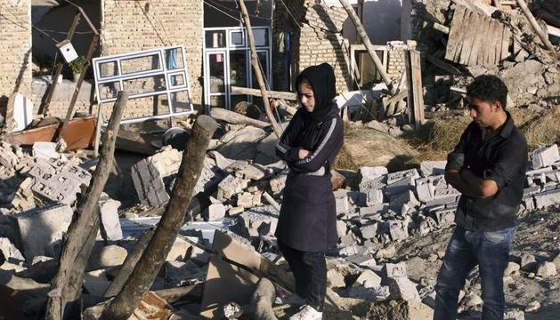 Dos hermanos caminan sobre los escombros de su vivienda de Bajeh Baj tras los terremotos sufridos en la zona