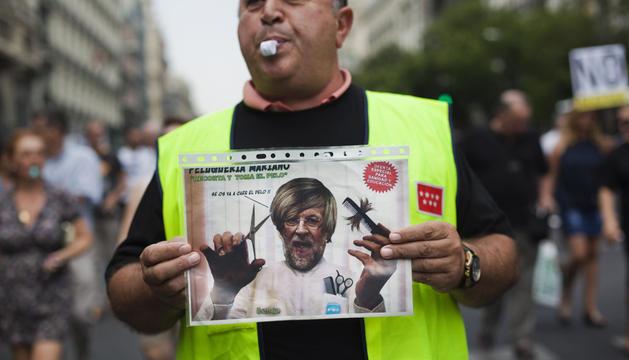 Un empleado público muestra una parodia de Mariano Rajoy en una protesta contra los recortes en Sanidad y Educación el pasado viernes en Madrid