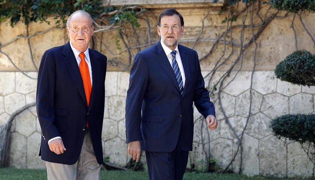 El rey Juan Carlos y Mariano Rajoy pasean por los jardines del Palacio de Marivent.