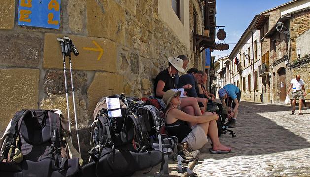 Un grupo de peregrinos hace cola en las puertas del albergue municipal de Estella para encontrar alojamiento.