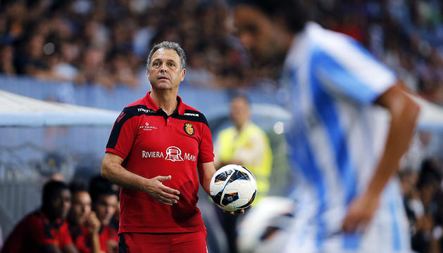 El técnico del Mallorca, Joaquín Caparrós, da instrucciones desde el banquillo con el malaguista Sergio Sánchez en primer término.