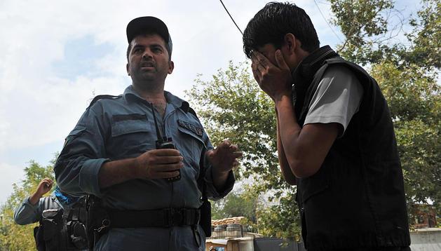 Un joven llora ante un agente de seguridad tras el ataque ocurrido en la zona diplomática de Kabul.