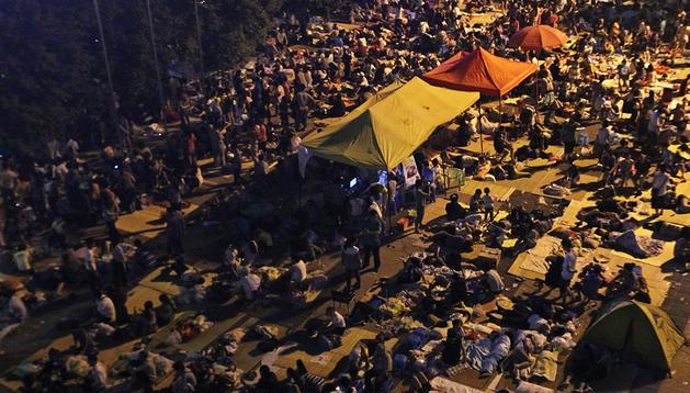 Personas desalojadas tras el terremoto acampan y pasan la noche en una plaza de la localidad de Yiliang.