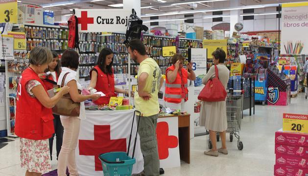 Unas voluntarias de la Cruz Roja reciben artículos escolares aportados por los ciudadanos en uno de los comercios participantes.