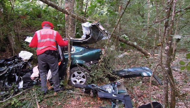Un agente de la Policía Foral toma notas junto al vehículo accidentado en la NA-411, a la altura de Eltzaburu.