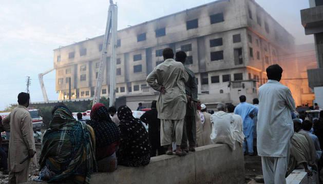 Varias personas observan la fábrica incendiada.