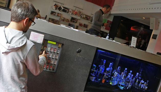 Una persona accede a la máquina de venta automática de tabaco en un bar de Pamplona.