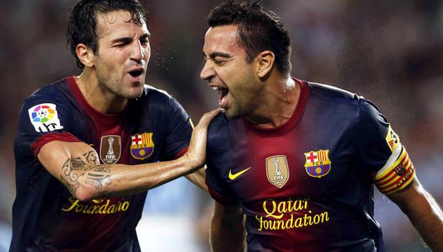El centrocampista del FC Barcelona, Xavi Hernández (dcha.), celebra su gol, primero de su equipo, con su compañero Cesc Fábregas durante el encuentro, correspondiente a la quinta jornada de Liga en Primera División, que disputan FC Barcelona y Granada CF.