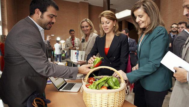 La presidenta de Castilla-La Mancha, Mª Dolores de Cospedal (izda.) y la ministra de Empleo y Seguridad Social, Fátima Bañez (dcha.), en el stand de Ecohuerta, ganador del I Premio de Emprendedores de Albacete.