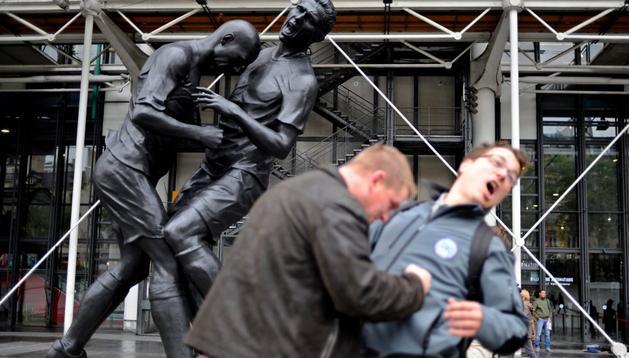 Dos visitantes posan junto a la escultura