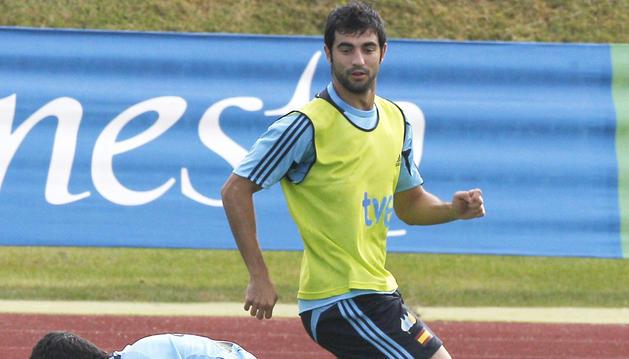 Sergio Busquets (izda.) y David Villa (dcha.) pugnan por un balón junto a Raúl Albiuol durante un entrenamiento de España en la Ciudad Deportiva de Las Rozas.