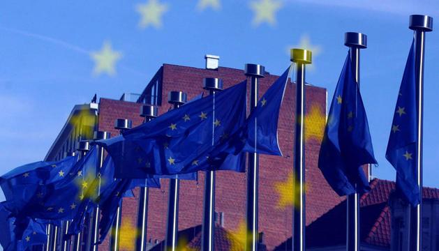 Estrellas de la bandera de la Unión Europea reflejadas en una ventana desde la que se ve el edificio del Consejo Europeo en Bruselas