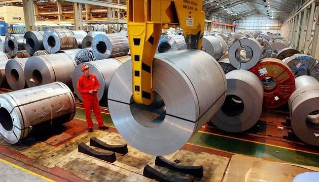 Un operario vigila un rollo de acero laminado en una fábrica