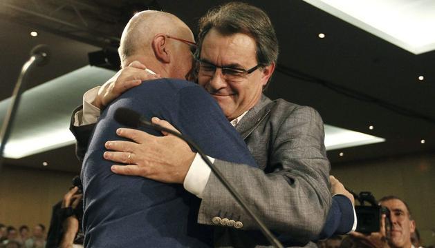 El líder de CIU y presidente de la Generalitat, Artur Mas, (derecha) abraza a Josep Antoni Duran i Lleida (izquierda) durante el acto en el que Mas ha sido proclamado cabeza de lista de CiU para las próximas elecciones al Parlamento de Cataluña