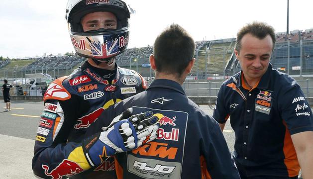 El británico Danny Kent (KTM) celebra con dos mecánicos la 'pole position'.