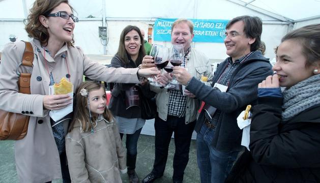 Un grupo de amigos brinda con uno de los vinos de la exposición mientras degustan un talo.