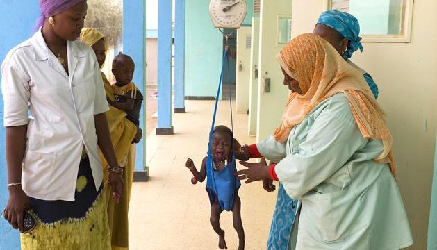 Varias personas pesan a un niño en un centro nutricional de Mauritania, uno de los países afectados por la hambruna.