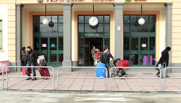 Varias personas frente a la fachada de la estación de tren de Pamplona.