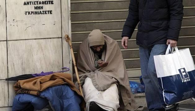 Un mendigo pide limosna en una calle del centro de Atenas.