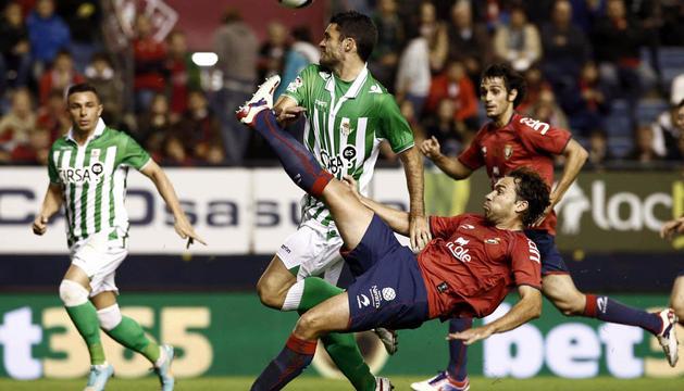 Lolo despeja el balón delante del bético Juan Carlos