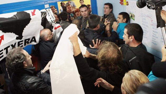 El equipo de seguridad y del PSE que acompañaba al lehendakari, Patxi López, y a su esposa, Begoña Gil, al colegio donde han depositado el voto, forcejea con un grupo de personas que les han recibido con carteles en apoyo de los presos de ETA.