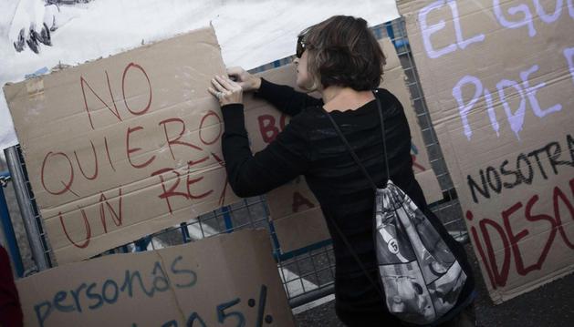 Una manifestante coloca un mensaje en una de las vallas policiales que rodea el Congreso de los Diputados.