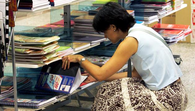 Una mujer ojea libros de texto en unos estantes.