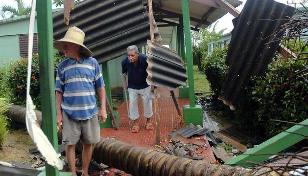 Dos hombres caminan bajo los escombros de su vivienda, destruida por el huracan