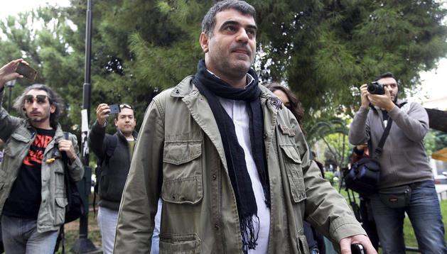 El periodista Kostas Vaxevanis (centro) es fotografiado por los medios a su llegada a los juzgados en Atenas (Grecia).