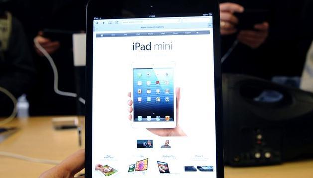 Varios clientes prueban la nueva tableta de Apple, iPad mini, en una tienda de la firma en Londres