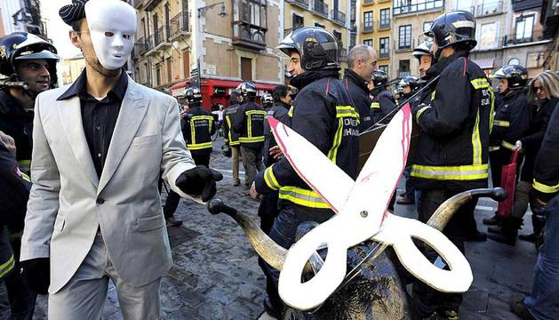 Bomberos del Gobierno de Navarra, trabajadores del 112 SOS-Navarra y administrativos de la Agencia Navarra de Emergencias (ANE) durante el encierro simbólico de toros que han protagonizado esta mañana por las calles de Pamplona, para protestar públicamente por el