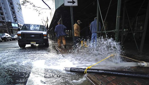 Unos trabajadores tratan de arreglar los desperfectos causados por el paso del Huracán Sandy.
