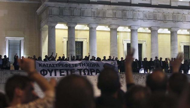 Parlamentarios griegos sujetan una pancarta en la que se puede leer