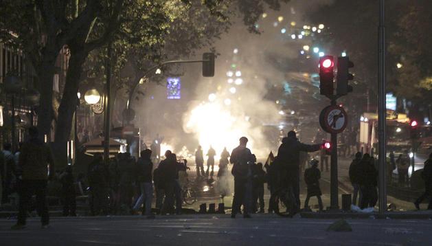 Vista del madrileño Paseo del Prado con las llamas producidas por la quema de mobiliario urbano.