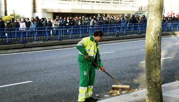 Un empleado del servicio de limpieza de Madrid barre una calle frente a una de las manifestaciones que hoy discurren por la capital