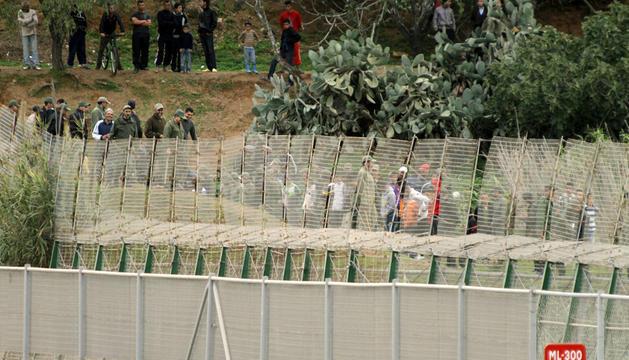 Varias personas, junto a la valla de Melilla