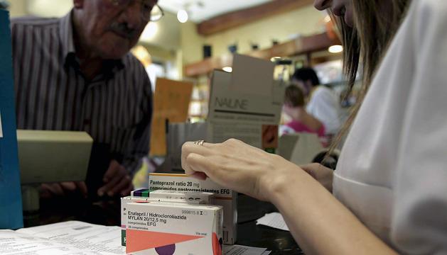 Un hombre adquiere varios medicamentos con receta en una farmacia de Barcelona.